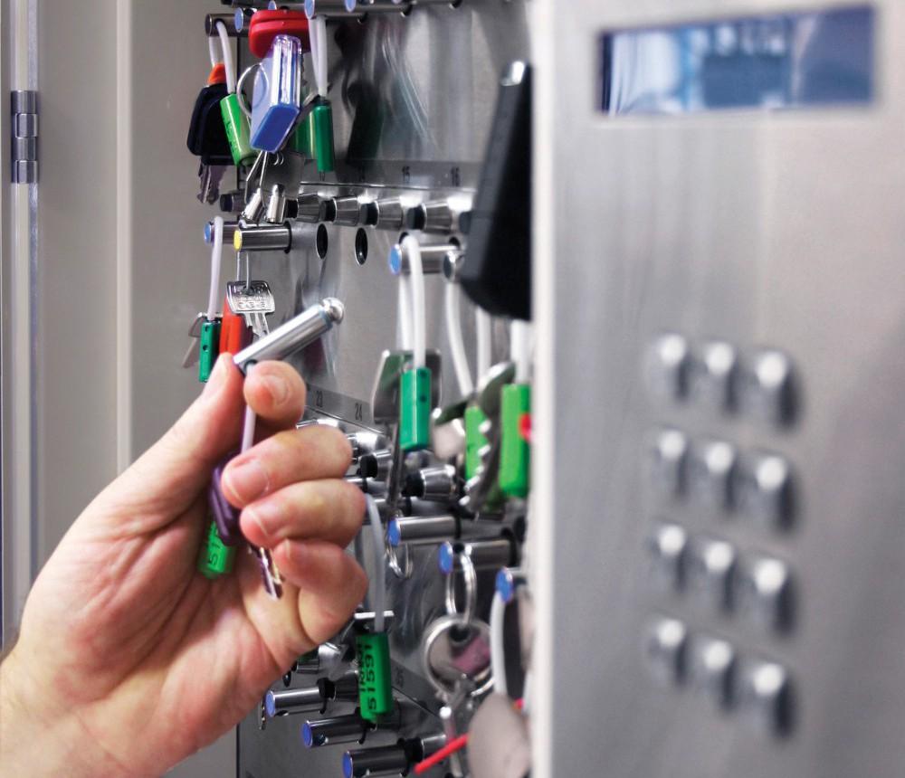 en hånd som tar ut en nøkkel fra nøkkelskap med kode